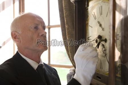 butler adjusting grandfather clock close up