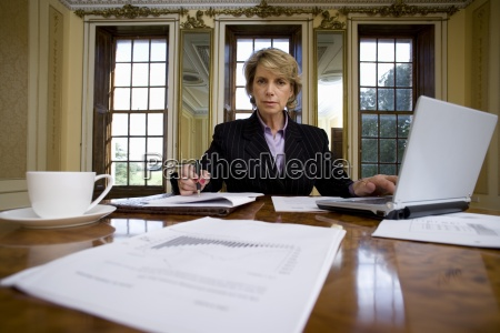 businesswoman with paperwork at table portrait