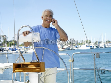 man using mobile phone on boat