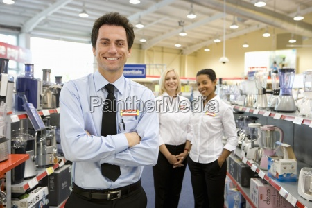 young salesman with arms crossed colleagues