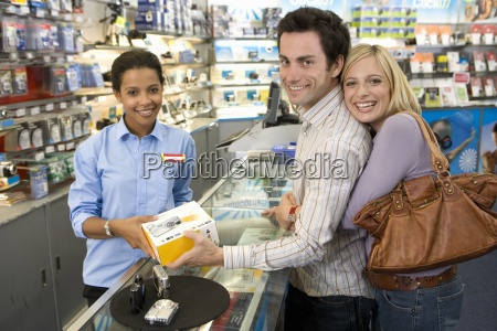 young couple with saleswoman buying camera