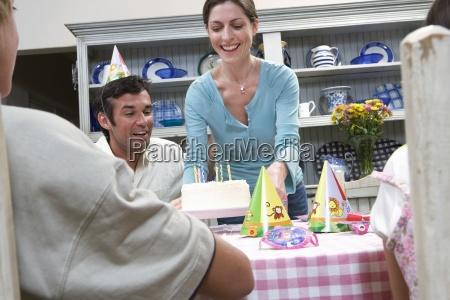 madre poniendo la torta de cumpleanyos