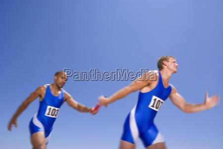 junge maennliche athleten vorbei staffellauf staffelstab