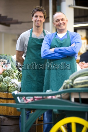 green grocers by shop smiling portrait