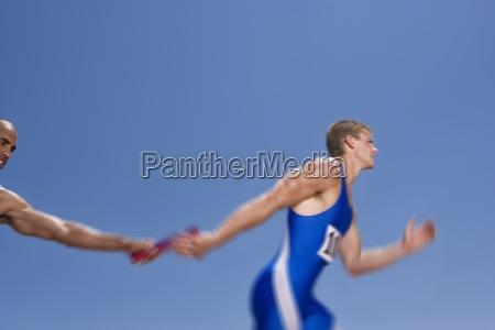 relay athleten vorbei taktstock bewegungsunschaerfe