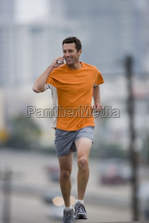 man running outdoors using mobile phone