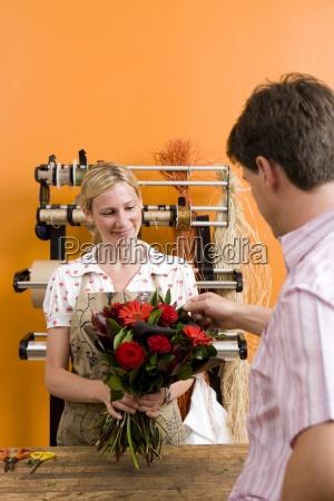 weibliche florist mit blumenstrauss fuer kunden