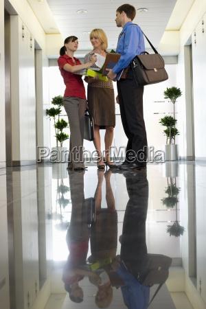 geschaeftsfrau zeigt papierkram zu kollegen in