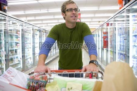 man lebensmitteleinkauf im tiefkuehlbereich
