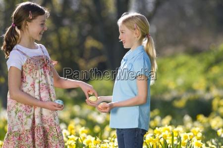 zwei junge maedchen die verzierten ostereier