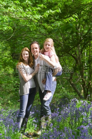 family posing in field of bluebell