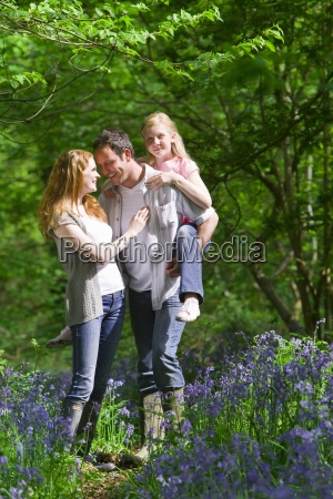 family walking in field of bluebell