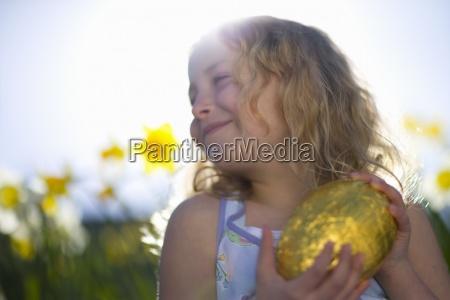 girl holding chocolate easter egg