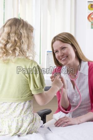 smiling nurse showing stethoscope to girl