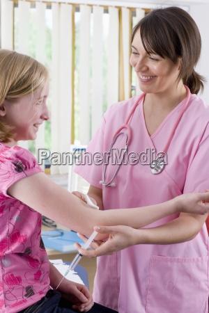 smiling nurse holding syringe and preparing