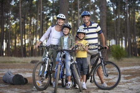 two generation family standing beside bicycles