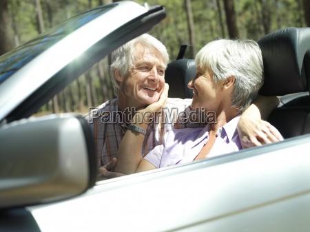 senior couple sitting in convertible car