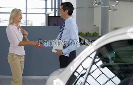 car salesman shaking hands with female
