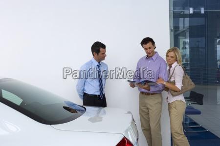 car salesman showing couple new car