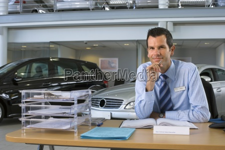 car salesman sitting at desk in
