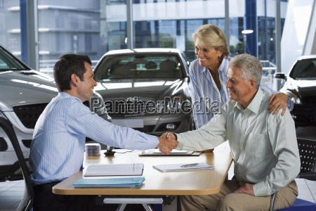 car salesman and senior couple sitting