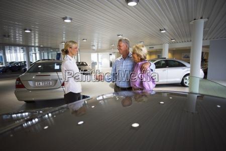 car saleswoman and senior couple standing