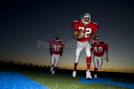 three american football players in red
