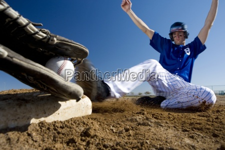 baseball player in blue uniform sliding