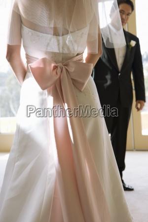 braut traegt hochzeitskleid mit rosa schleife