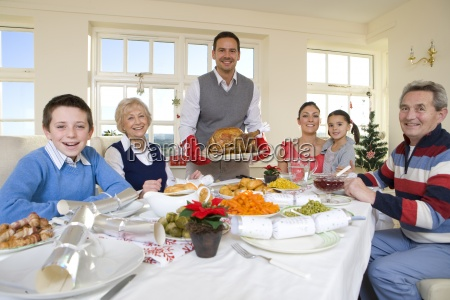 multi generation family eating christmas dinner