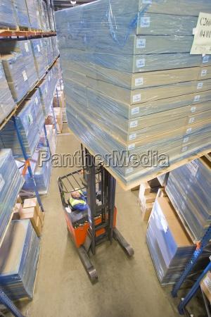 lagerarbeiter boxen auf gabelstapler bewegen