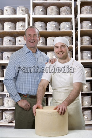 portrait of smiling cheese makers binding