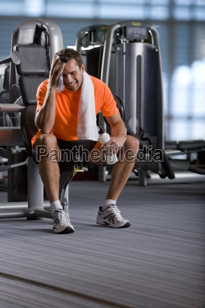 smiling man sitting on exercise equipment