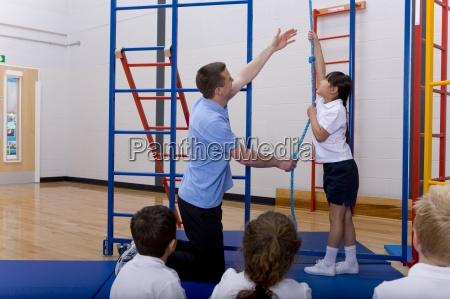 gym teacher in school gymnasium with