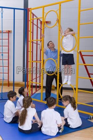 gym teacher helping student climb gymnasium