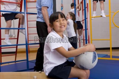 school girl sitting in gymnasium holding