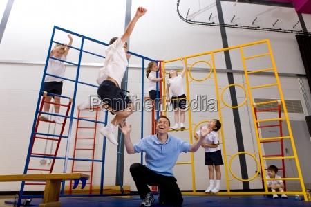 gym teacher watching school boy jumping
