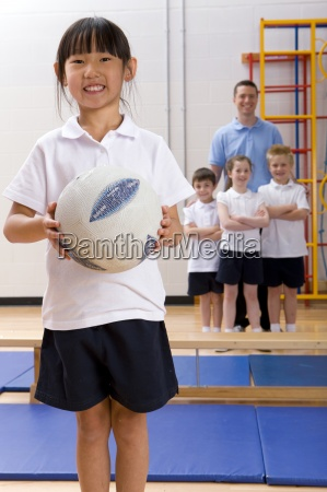 school girl holding ball in school