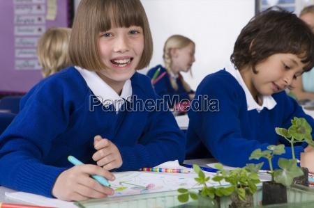 schule maedchen in notebook mit pflanzenkeimlingen