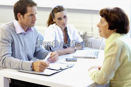ein bewohner im gespraech mit pflegehelferinnen