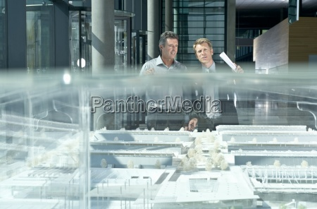 zwei geschaeftsleute ein architektonisches modell im