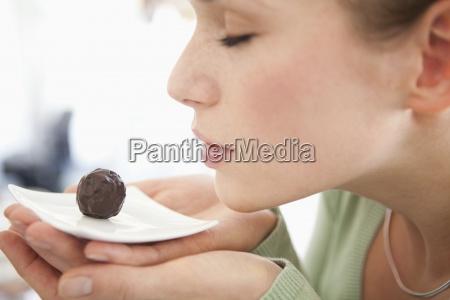 eine frau riechen eine schokolade auf