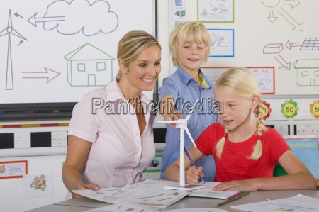 curious students and teacher examining model