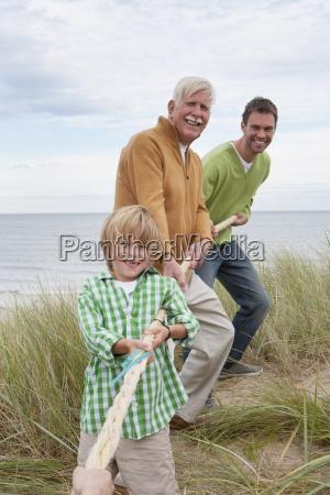 maennerfamilie nimmt teil in tug of