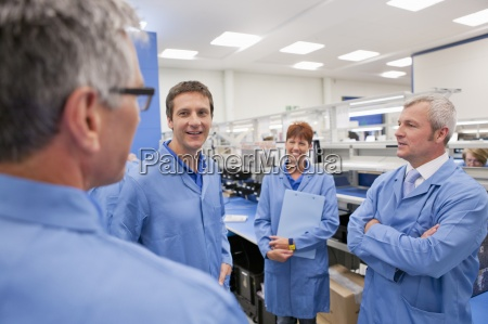 technicians in lab coats talking in