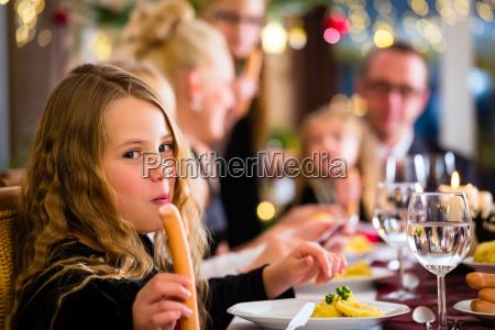 familie bei weihnachtsessen wuerstchen und kartoffelsalat