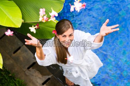 frau mit blumen am tropischen pool