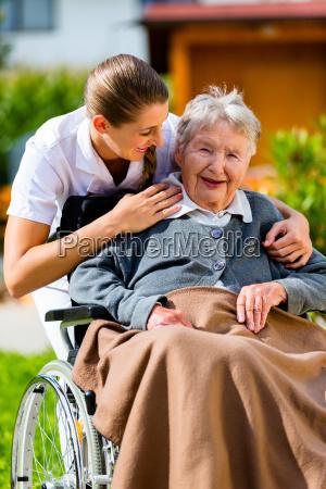 seniorin mit pflegerin im garten von
