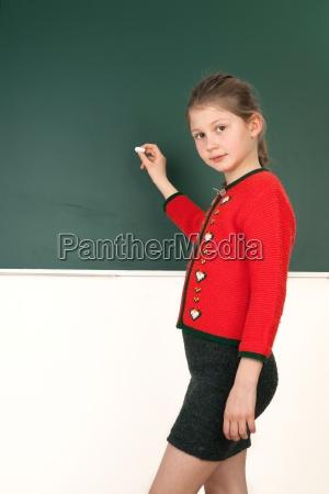 schuelerin steht im unterricht vor tafel