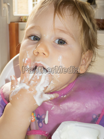 baby isst joghurt mit der hand